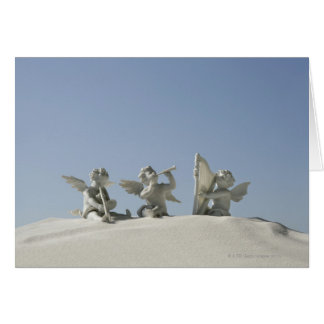 Estatuetas do anjo com instrumentos musicais sobre cartão comemorativo