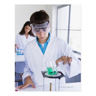 Estudante que faz a experiência 2 da ciência cartao postal