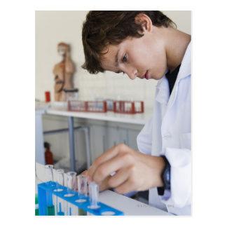 Estudante que faz a experiência da ciência cartão postal