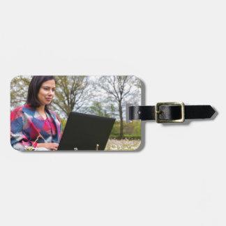 Etiqueta De Bagagem A mulher senta-se com o laptop no prado de