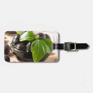 Etiqueta De Bagagem Azeitonas pretas em uma mesa e em copos do vidro