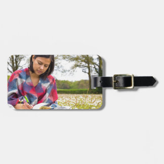 Etiqueta De Bagagem Escrita da mulher no prado com flores do primavera
