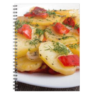 Fatias de batatas e de pimentas stewed no cadernos espiral