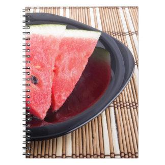 Fatias de melancia vermelha em uma placa preta caderno espiral