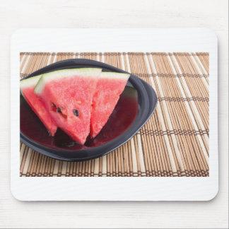 Fatias de melancia vermelha em uma placa preta mouse pad