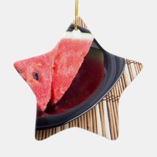 Fatias de melancia vermelha em uma placa preta ornamento de cerâmica estrela