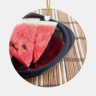 Fatias de melancia vermelha em uma placa preta ornamento de cerâmica redondo