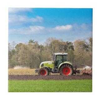 Fazendeiro no trator que ara o solo arenoso no