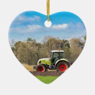 Fazendeiro no trator que ara o solo arenoso no ornamento de cerâmica coração