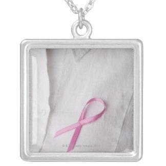 Feche acima da fita da consciência do cancro da colar banhado a prata