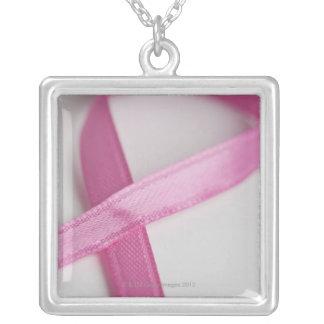 Feche acima da fita da consciência do cancro da colar com pendente quadrado