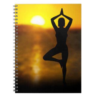 Fêmea da ioga pelo oceano no caderno espiral do