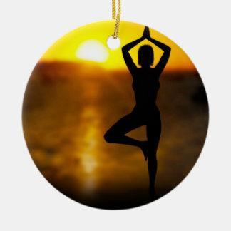 Fêmea da ioga pelo oceano no ornamento do por do