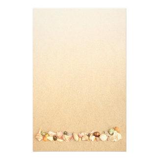 Fileira dos Seashells na areia da praia Papelaria