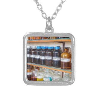 Fileiras dos produtos químicos fluidos em umas colar banhado a prata