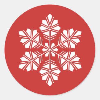 Floco de neve branco na etiqueta vermelha do Natal