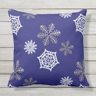 flocos de neve dourados e brancos contra o azul da almofada para ambientes externos