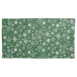 Flocos de neve nas fronha de almofada verdes,