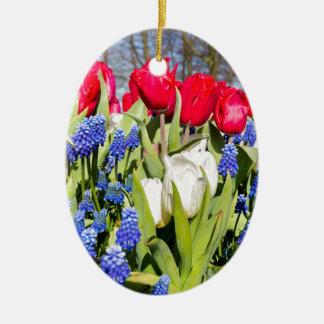 Flores azuis brancas vermelhas na estação de ornamento de cerâmica