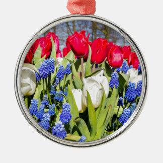 Flores azuis brancas vermelhas na estação de ornamento de metal