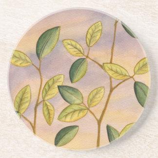 Folhas verdes e amarelas no fundo do por do sol porta copos de arenito