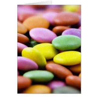 Foto detalhada de bombons coloridos do chocolate cartão