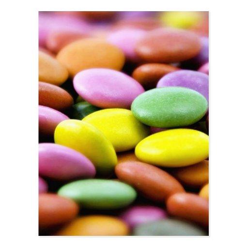 Foto detalhada de bombons coloridos do chocolate cartoes postais