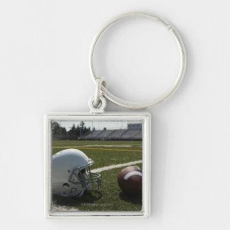 Futebol e capacete de futebol no campo de futebol chaveiro