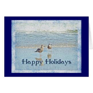 Gaivotas e cartão das ondas boas festas