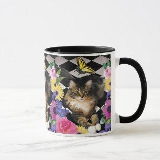 Gato bonito do gatinho na caneca do jardim da