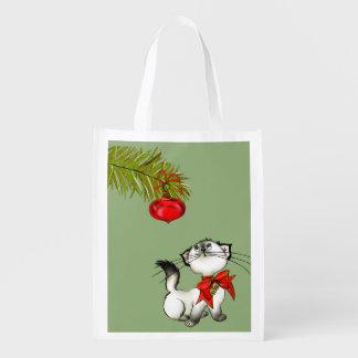 Gato brincalhão do gatinho em um arco vermelho do sacolas ecológicas
