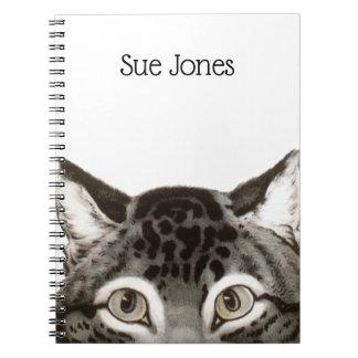 Gato que espreita o caderno espiral