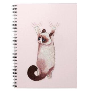 Gato que pendura sobre pelo caderno espiral das
