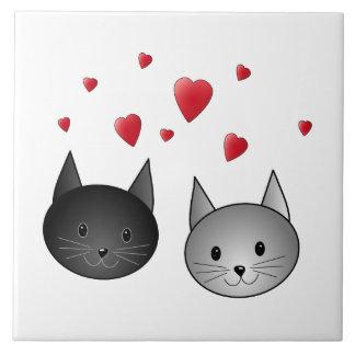 Gatos pretos e cinzentos bonitos, com corações azulejos de cerâmica
