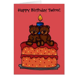 gêmeos da menina em um cartão do bolo de aniversár
