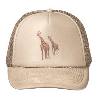 Girafas da mãe e da criança que tiram chapéus boné