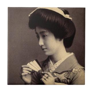 Gueixa com o fã de papel de dobramento em Japão