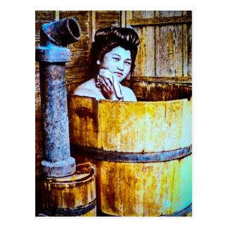 Gueixa do vintage que banha-se em uma cuba de cartão postal