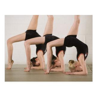 Gymnasts que levantam upside-down cartão postal