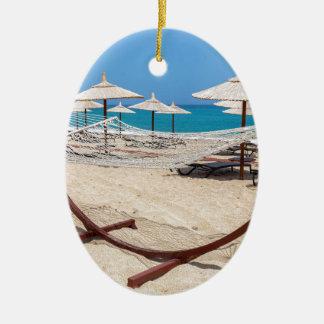 Hammock com os guarda-chuvas de praia na costa ornamento de cerâmica