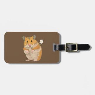 Hamster pequeno bonito que guardara uma flor etiqueta de bagagem