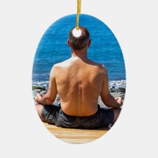 Homem que meditating na praia e no mar ornamento de cerâmica