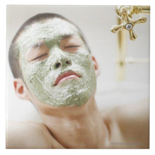 Homem que relaxa em uma banheira com uma máscara f azulejo