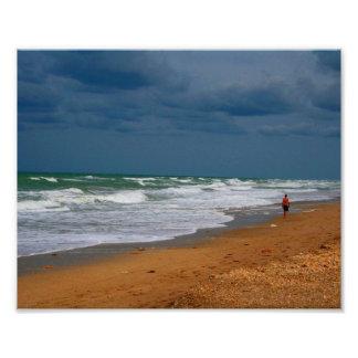 Homem solitário que anda na praia tormentoso impressão de foto