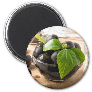 Imã Azeitonas pretas nos copos de vidro com óleo