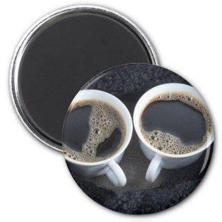 Imã Duas chávenas de café envolveram um lenço preto de
