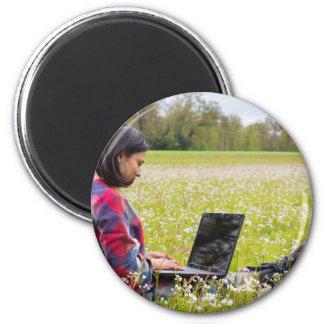 Imã Mulher que senta-se com o laptop no prado do