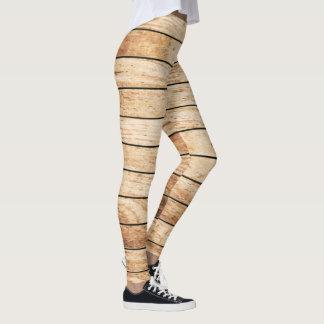 Legging Contra o painel da madeira da grão