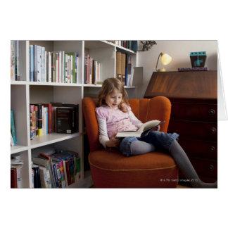 Leitura da menina pela estante cartão