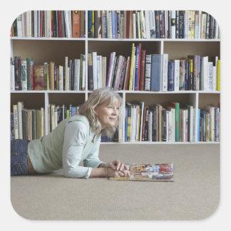 Leitura da mulher mais idosa por estantes adesivos quadrados